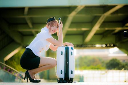 带着手提箱的亚洲女孩空姐