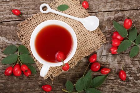 与野蔷薇浆果在桌子上的白色茶杯