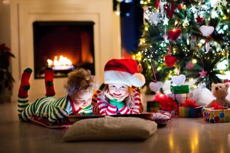 在圣诞树下新年的服装的小孩