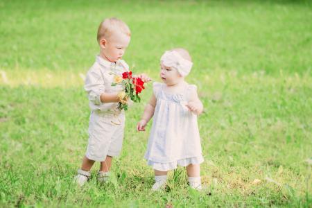 一个小男孩给一个女孩一束野花