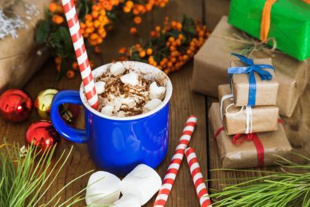 与礼物为新年的桌子上的棉花糖甜饮料