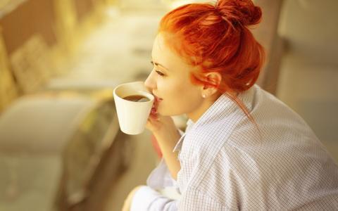明亮的红发女孩穿着衬衫喝咖啡