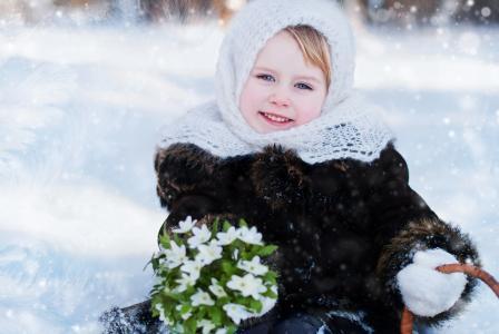 有一束雪花莲的小蓝眼睛的女孩在冬天