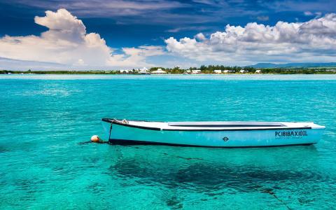 在蓝色清楚的水的白色小船