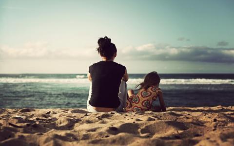 一个女人和她的女儿正坐在海边的沙滩上