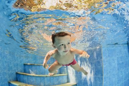 小男孩在游泳池里的水下游泳