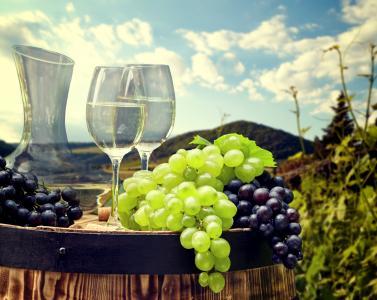 葡萄的蓝色和白色葡萄与木制酒桶上的酒杯