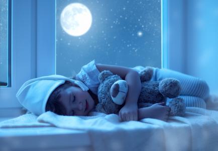 一个穿着睡衣的小孩在月亮的背景下睡着一个柔软的玩具
