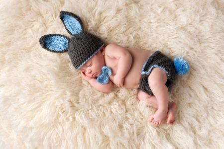 在一个被编织的野兔服装的睡觉的婴孩