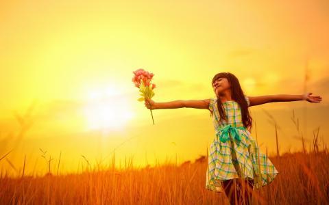 有一束花的女孩站在田野里