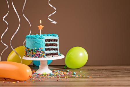一支蜡烛和气球的生日蛋糕