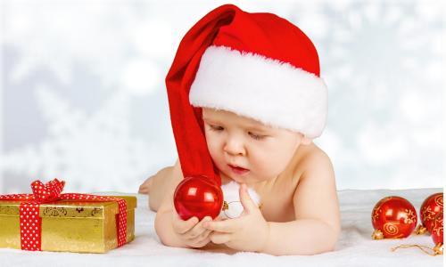 一个红色圣诞帽的婴儿与圣诞节球为新的一年