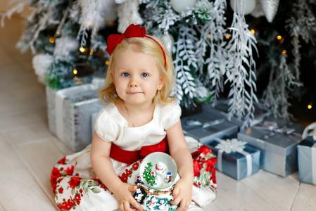 小金发女孩坐在圣诞树下的礼物