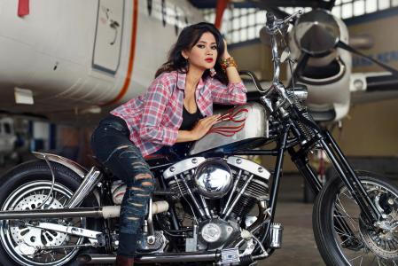 在摩托车上的牛仔裤的年轻亚洲女孩