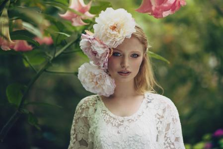 在她的头发大牡丹白色连衣裙的漂亮女孩