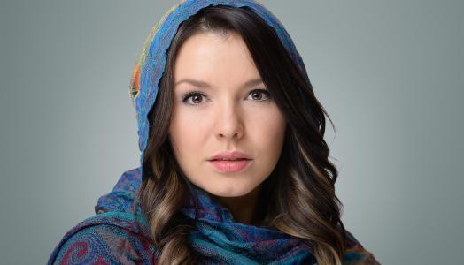 一个年轻的棕色眼睛女孩的脸在灰色的背景上的围巾