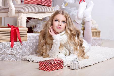 与礼物的白色毛衣的漂亮金发女郎