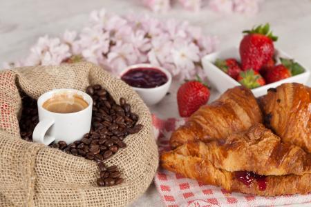 一杯咖啡与咖啡豆和新鲜羊角面包一袋