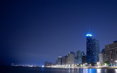 城市在晚上在河岸上点燃
