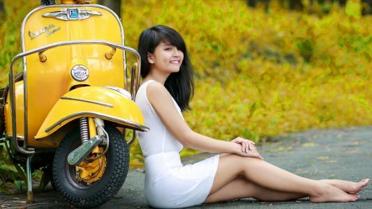 亚洲女孩在黄色的滑板车