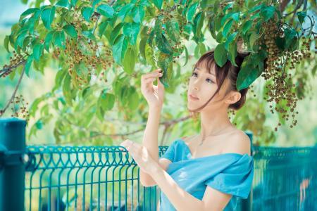 年轻漂亮的亚洲女孩站在绿叶的分支