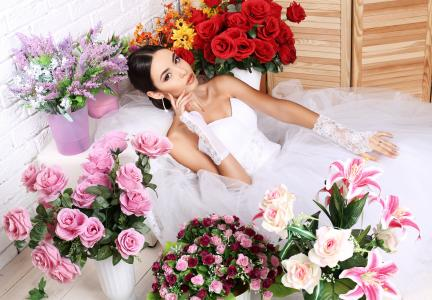 美丽的新娘女孩穿着白色连衣裙与花束