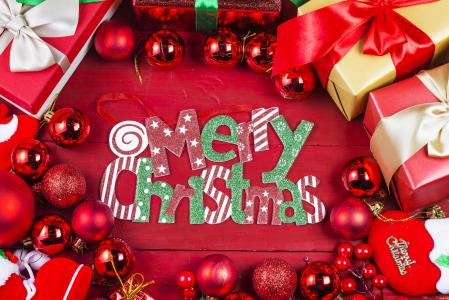 快乐圣诞假期题字与玩具和礼品的红色背景上