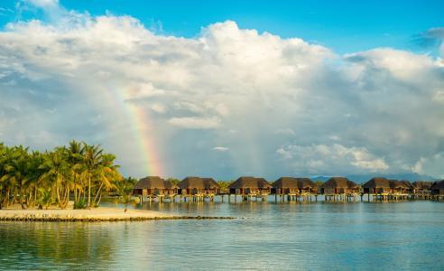 平房在热带海滩上与彩虹多云的天空下的水中