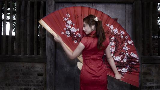 美丽的亚洲女孩穿着红色大风扇
