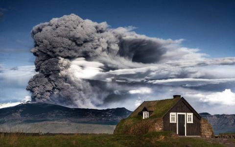 在冰岛的房子背景下的一个喷发的火山
