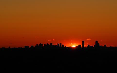 太阳躲在黑暗摩天大楼的边缘