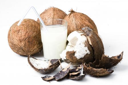 椰子牛奶在玻璃和椰子在白色背景上