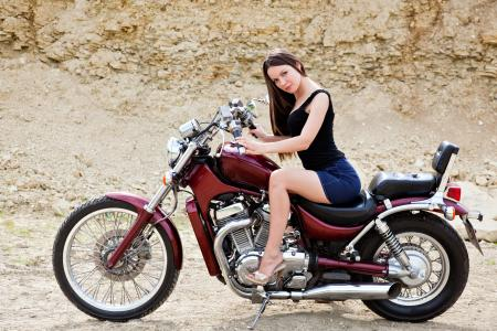 优雅的年轻黑发女孩坐在一辆红色的摩托车