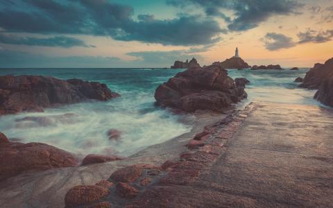 路堤背景上的一座灯塔在一块岩石上