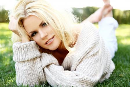 一件白色毛衣的金发女孩躺在绿色的草地上