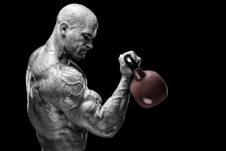 强壮的男子哑铃在他的怀里强健的男性健美运动员