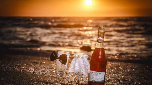一瓶葡萄酒和两个沙滩上的眼镜