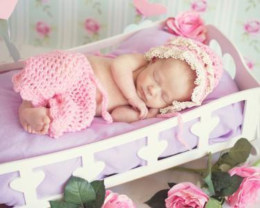 睡觉的女婴在摇篮里的粉色西装