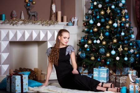 在一棵圣诞树下的黑色礼服的漂亮女孩