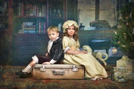 小男孩和女孩在老式的服装坐在行李箱上