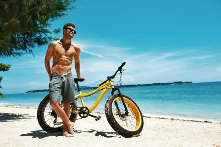 英俊的肌肉男与一辆自行车在海滩上