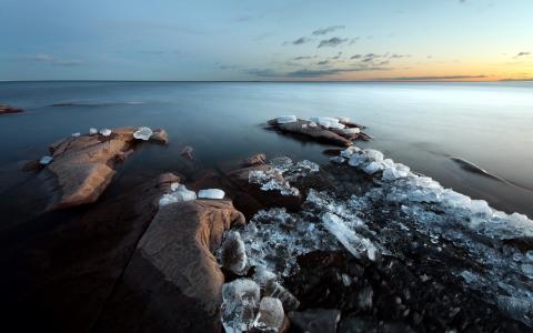 冰块在岸边的岩石上