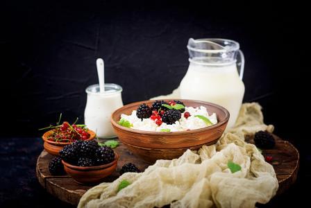 与浆果和新鲜的牛奶在桌上的早餐奶酪