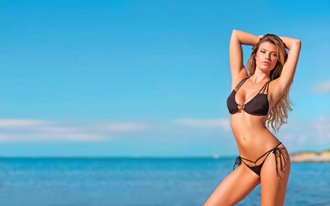 在海洋背景上的黑色泳衣热辣的年轻女孩