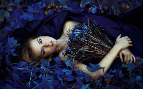一束鲜花在蓝色的花朵中的女孩